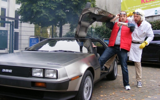 Marty McFly und Doc Brown vor dem DeLorean.